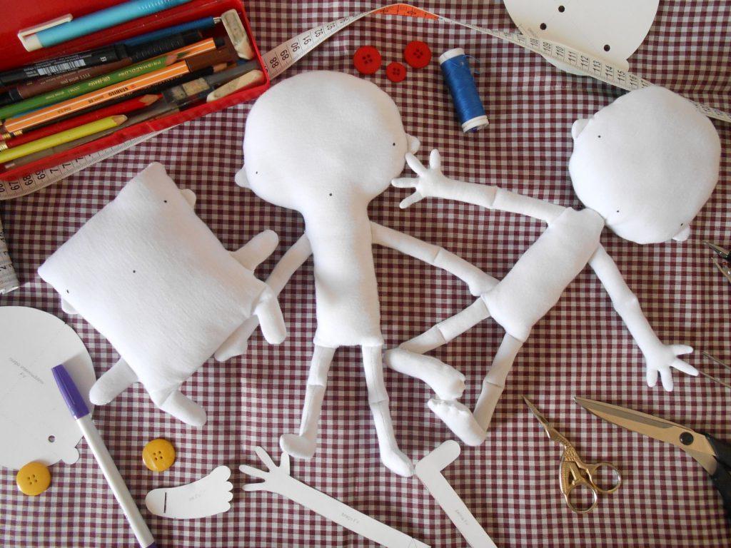 """Ao centro três bonecos brancos  com rosto minimalista formado por apenas 3 pontos, sendo dois para os olhos e um para boca.  Da esquerda para direito - Um boneco quadrado com bracinhos e pernas tipo """"toquinho""""  - Um boneco com o corpo em formato de lupa, com braços com mãos em formato de luva de tirar comida do forno e perna e L  - Boneco com cabeça e troncos individualizados. A braços possuem mãos com dedos separados e as pernas possuem pés com dedos.  Ao redor estão materiais de desenho e costura. No sentido horário, começando da esquerda superior: um estojo com diversos lápis e canetas, fita métrica, três botões, um carretel de linha, um pedaço de papel (molde) a ponta de uma tesoura grande, uma tesoura pequena em forma de pássaro, o molde de uma perna com pé em L, um molde de um braço com dedos separados, um molde de um pé, um botão, uma canetinha, outro botão e um pedaço de outro molde.  Tudo isso sobre um fundo de tecido com padronagem xadrez."""