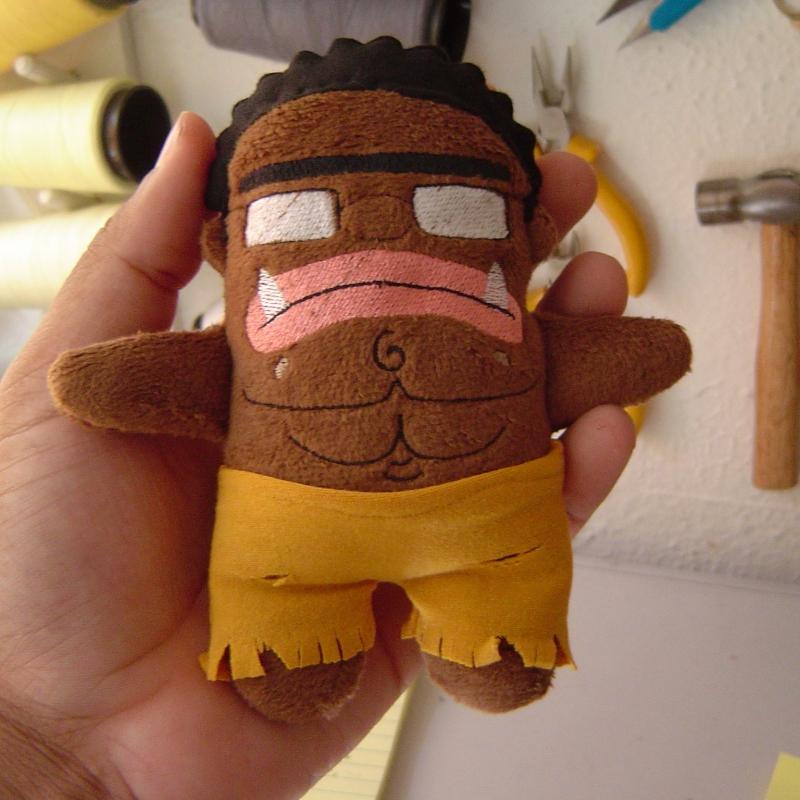 Boneco com cor marrom, usando óculos, cara de bravo e caninos pontudos. No meio do peito há bordados para simular abdome defiido. Ele usa uma calça amarela mostarda ragada