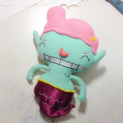 Sereia feliz com pele verde água e cabelo rosa chiclete. A causa é de cetim vinho