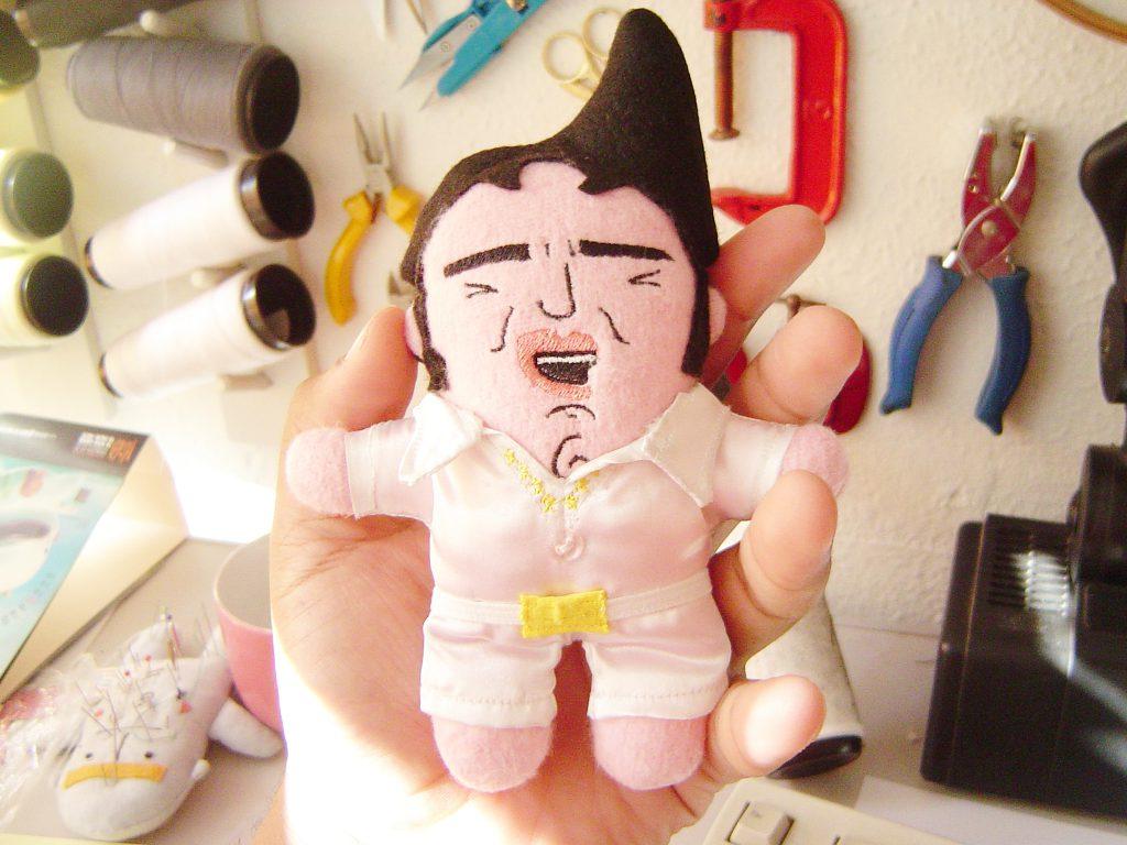 Ao centro da imagem uma mão segurando uma mini-mi do Elvis Presley. Ao fundo diversas ferramentas