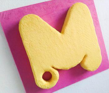 Símbolo do .marcamaria (o .M) em pelúcia, em formato tridimensional.
